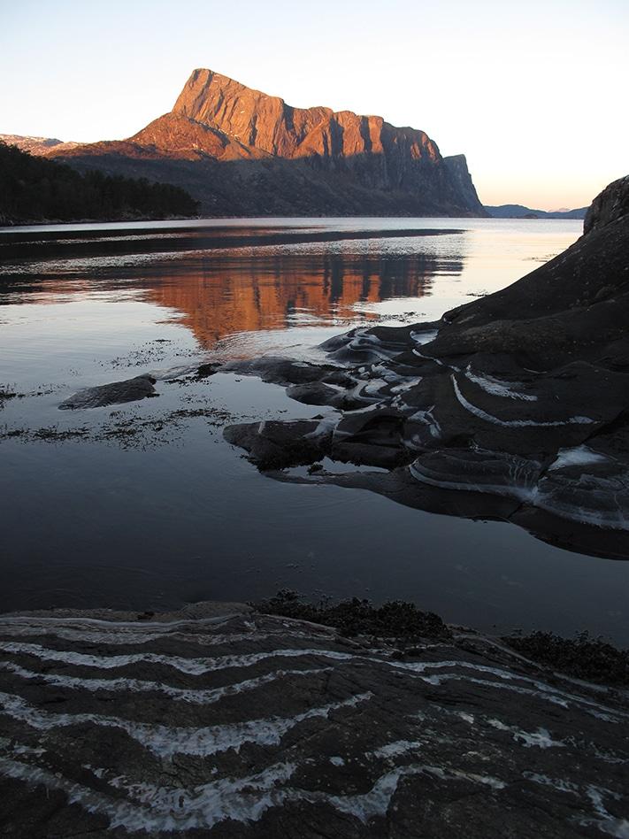 Toppen av Lihesten i Hyllestad, ytterst i Sogn og Fjordane, ble en gang avsatt som stein og grus i daler mellom høye fjelltopper i Den kaledonske fjellkjeden for 400 millioner år siden. I dag er fjellkjeden borte, men den gamle ura står igjen som et majestetisk landemerke i konglomerat. Under konglomeratet ligger omdannete sedimentære og magmatiske bergarter som en gang ble dannet på havbunnen utenfor Laurentia. Grensen mellom de to geologiske enhetene kalles Nordfjord-Sogn skjærsone. Lihesten utgjør en del av Solundbassenget, et av flere devonbassenger langs vestlandskysten (se Landet blir til, NGF 2006, Kap 7: Fjellkjeden går til grunne). Foto: Rolv Dahl