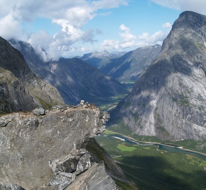 """Romsdalen betyr """"Raumas dal"""", etter den strie elva som renner gjennom dette helnorske landskapet. Det trange dalføret, som strekker seg fra Åndalsnes i nord til Lesjaskogsvatnet i sør, er viden kjent for de majestetiske toppene Trolltindene og Romsdalshorn, samt Trollveggen hvor det stadig løsner små skred (GEO 02/1998). Trollveggen har oppnådd internasjonal berømmelse fordi vi her finner Europas høyeste overhengende stup med et loddrett fall på mer enn 1000 m, men også fordi den nettopp derfor blir oppsøkt av både base- og fallskjermhoppere som setter livet til på sin jakt etter spenning. Rett sør for disse berømte fjellene, litt lenger inn i dalen, er det enda mer spenning, for her lurer skredfaren. Gapende sprekker i fjellsiden og brede rasvifter i dalbunnen vitner om ustabile fjellmasser. Mens lokalbefolkningen er godt kjent med små hyppige skred, sier geologene nå at store biter av fjellene like sør for Trolltindene kan gli ut. De små utrasningene kan være et forvarsel, en påminnelse om at større skred kan være på gang. Foto: Halfdan Carstens"""