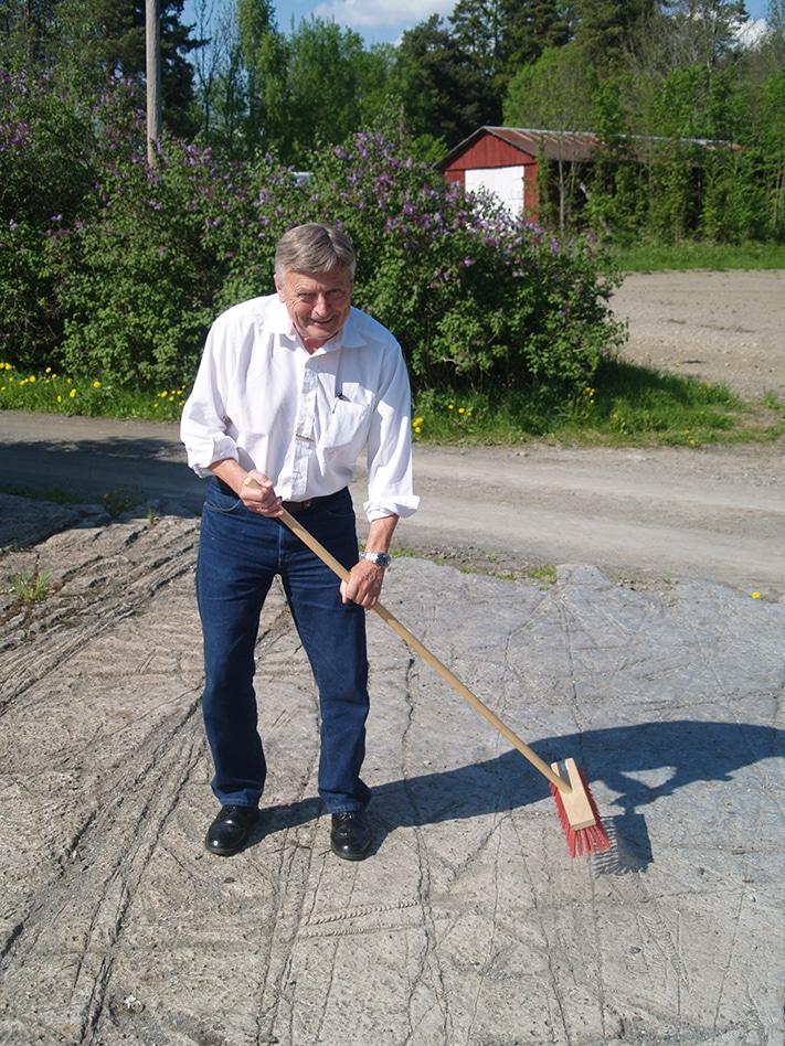 """En ekte nyinnkjøpt piasavakost gjør susen når den flotte «fossilflaten» utenfor Hokksund skal renses. """"Amatørpaleontolog"""" Kjell G. Finstad sparer ikke på energien. Foto: Halfdan Carstens"""