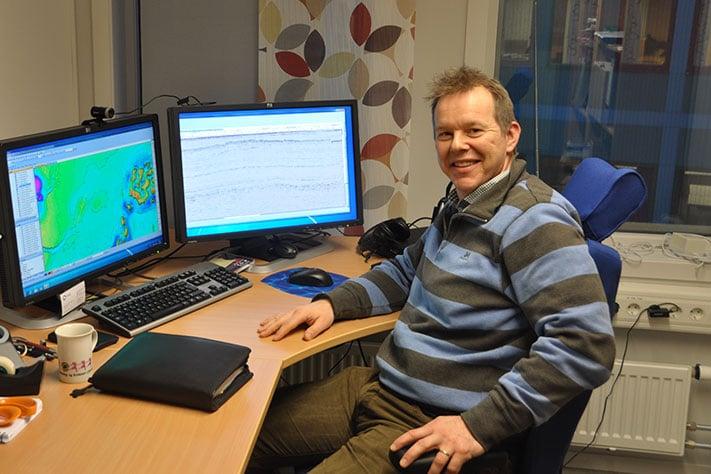Tommy Samuelsberg har flyttet tilbake til Tromsø. Det er leteaktiviteten i Barentshavet som har gjort det mulig. I løpet av drøye fem år har han allerede rukket å ha to forskjellige arbeidsgivere i Nord-Norges hovedstad. Skjermen til høyre viser en seismisk linje gjennom gassfunnet Norvarg. Foto: Halfdan Carstens