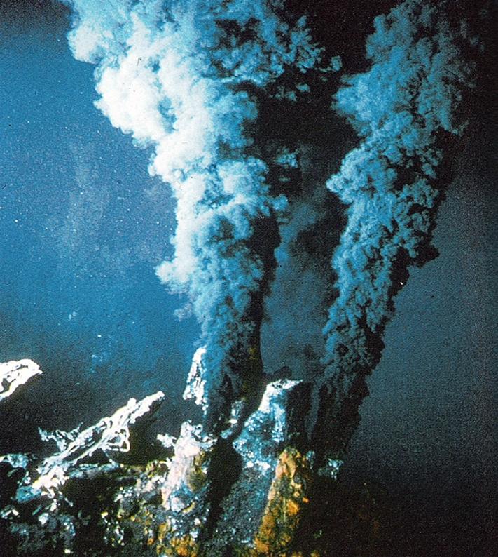 """Samme år (1977) som gruvedriften på Røros ble nedlagt, ble det for første gang funnet rykende skorsteiner (""""black smokers"""") som gir opphav til massive sulfidforekomster på osean skorpe (""""seafloor massive sulfide deposits"""", forkortet SMS-forekomster). Varme fluider strømmer opp av skorsteinene med en hastighet på 1-5 m/s. Det er altså store volumer det dreier seg om, og skorsteinen kan vokse så mye som 30 cm/dag.  Foto: Nautilus Minerals"""