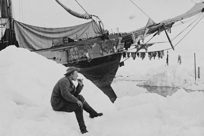 """Fridtjof Nansen sitter og røyker pipe ved Fram 16. juni 1894. """"Og over alt annet, en uovervinnelig lyst til å lære å kjenne og forstå alt han så i naturen"""". Sitat fra W. Werenskiold, 1961, om Fridtjof Nansen som vitenskapsmann. Foto: Nasjonalbiblioteket, Billedsamlingen"""