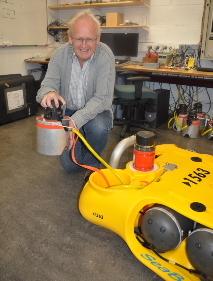 """Eivind Berg er oppfinner. Ingen bestrider at han er mannen bak 4C-seismikk etter at ideen ble sådd sent på 1980-tallet. Her står han med en CASE Abyss (""""Cableless Seismic"""") node hvor den gule boksen med hard-disk, elektronikk og batterier ligger på bunnen, mens den grå sylinderen inneholder tre geofoner, en hydrofon og inklinometer og er plantet ned i bunnen for å sikre et godt signalmottak. Foto: Halfdan Carstens"""
