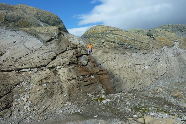 Serpentinitt (grønn og brun bergarter øverst i bildet) erstattes av magnesittrik kleberstein (grå bergart i nedre halvdel av bildet). Fra Linnajavriområdet i Nordland. Foto: Oliver Plümper, PGP.