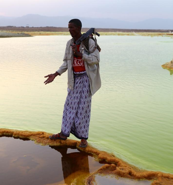 Vannet med svovel og jernrike utfellinger tilhører den varme kilden på toppen av Mount Dallol. I bakgrunnen ser vi det etiopiske høylandet som ligger utenfor riftdalen. Foto: Jørgen Stenvold