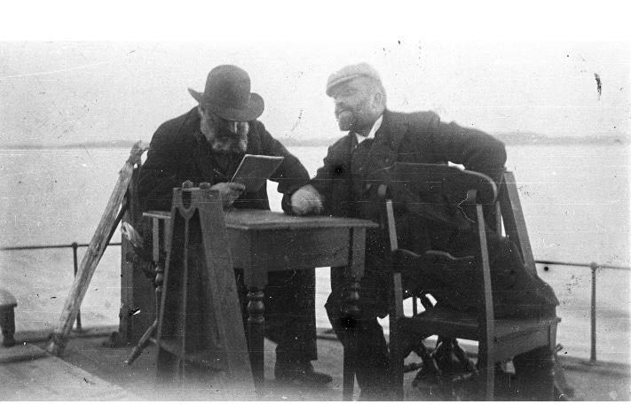 Kan hende er de på vei til et politisk møte, de to venstremennene Amund Helland (med bok i hånden) og Viggo Ullmann (1848–1910). Bildet er tatt en gang mellom 1900 og 1919. På det tidspunktet var Ullmann, som opprinnelig var skolemann, stortingsrepresentant for Venstre. Foto: Museum for universitets- og vitenskapshistorie, Universitetet i Oslo.