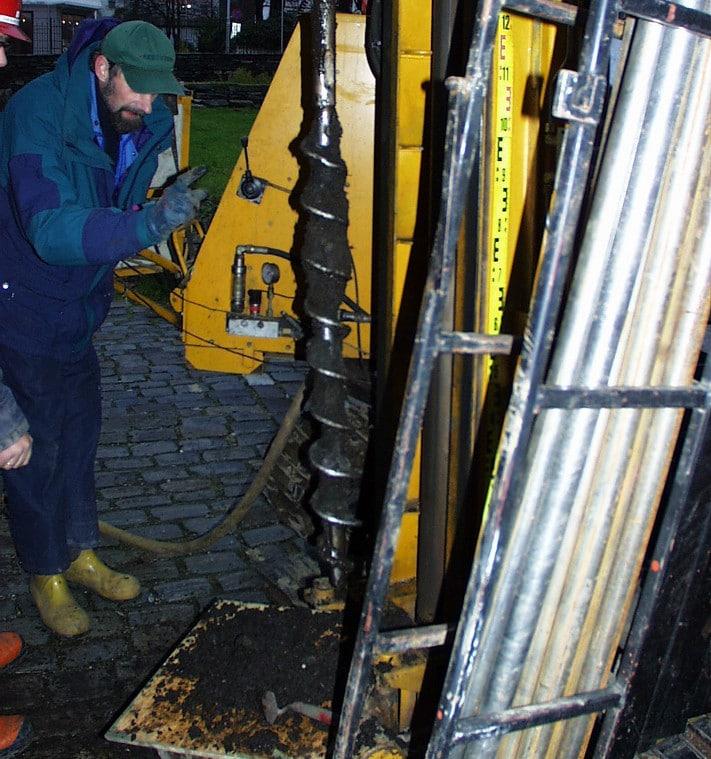 Ved Bugården (nordhjørnet Bryggen) er grunnvannssenkning størst og nedbryting mest dramatisk. Derfor monterte Multiconsult A/S en miljøbrønn i dette området. Arkeolog Rory Dunlop (NIKU) inspiserer og dokumenter prøvene fra kulturlag.  Kilde: Jann Atle Jensen, Multiconsult AS.