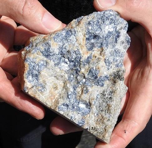 Det grå og glinsende mineralet har blitt avsatt på tynne kvartsganger som gjennomskjærer vertsbergarten (granitt). Massive klumper av molybdensulfid på flere tonn har også blitt funnet. Foto: Halfdan Carstens