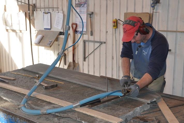 De fleste av de 36 ansatte i Oppdal Sten er steinhoggere og jobber i den store produksjonshallen midt i Oppdal sentrum. Her ser vi hvordan det skapes en knekt kant som på mange vis er varemerket for Oppdalskifer. Foto: Halfdan Carstens