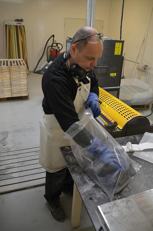 Juris Krastins legger stein fra et lite intervall i plastposer som sendes til et sertifisert laboratorium. Posene anonymiseres slik at ingen på laboratoriet skal falle for fristelsen til å kjøpe aksjer i Nordic Mining hvis analyseresultatene er veldig oppløftende. Foto: Halfdan Carstens